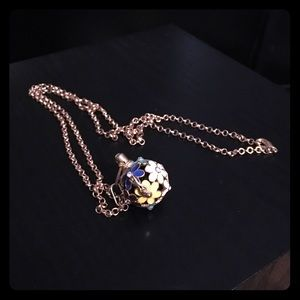 Gold colored necklace with flower cage and marble